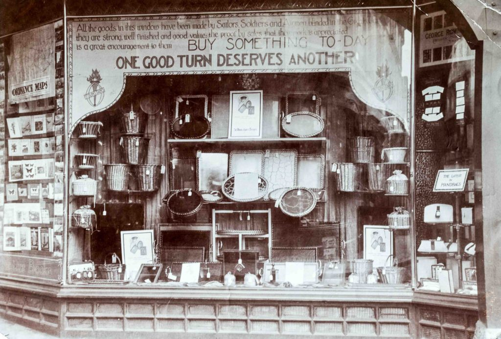 A picture of the St Dunstan's shop on Regent's street, showing windows full of trays, baskets, and other goods made to support servicemen blinded in the First World War.